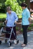 Nurse watches as an elderly woman walks Stock Photos