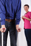 Nurse watching disabled man on crutches Royalty Free Stock Images