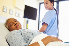 Nurse Watching Sleeping Senior Woman Patient In Hospital. Room Wearing Scrubs Stock Image