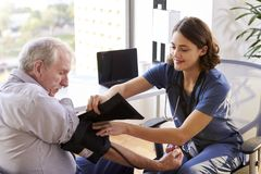 Free Nurse Wearing Scrubs In Office Checking Senior Male Patients Blood Pressure Stock Photos - 144590143