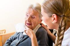 Nurse wiping mouth of senior woman in nursing home Stock Image