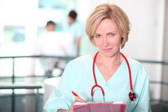 Nurse writing on clip-board Royalty Free Stock Image