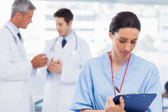 Nurse writing on a clipboard while doctors are talking together Royalty Free Stock Image