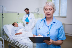 Nurse writing on clipboard. In hospital room Stock Images