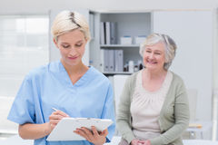 Nurse writing on clipboard while patient sitting in clinic Royalty Free Stock Image