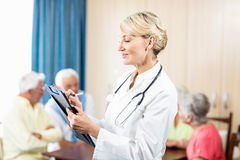 Nurse writing on clipboard. In a retirement home Stock Image