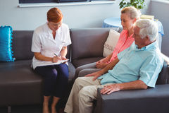 Nurse writing on clipboard. In a retirement home Stock Photo
