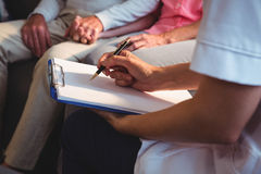 Nurse writing on clipboard. In a retirement home Royalty Free Stock Photography