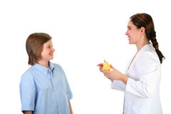 Nurse and young boy. Nurse showing young teenage vitamin pills and fruits - isolated on white Royalty Free Stock Photo