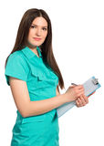 Nurse or young doctor in uniform with clipboard writing Stock Images