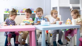 Nursery babies eating food. Kids have lunch in daycare stock photo