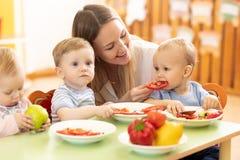 Babies eating healthy food in kindergarten. Nursery babies eating healthy food in kindergarten royalty free stock image