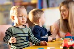 Nursery children playing with teacher in kindergarten stock images