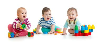 Nursery babies playing with color toys isolated on white background stock images