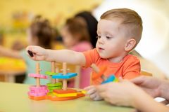 Child boy together with teacher playing educational toys at sunny day in nursery royalty free stock photography