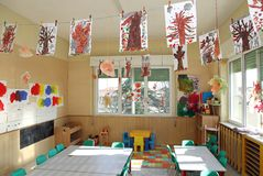 Nursery class of children with many drawings of trees hanging fr. Kindergarten classroom of children with many drawings of trees hanging from the ceiling stock photography