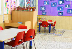Nursery class with small red chairs and children's drawings Stock Photo
