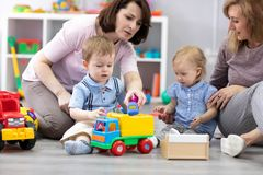 Nursery kids playing with toys. Mothers communicate and watch over their children stock photo