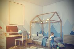 Baby boy s room with a computer, side view toned. Nursery with a mountain wallpaper, a wooden floor, a double bed with a house like roof and a computer desk. A Stock Photos
