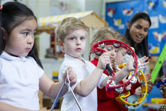 Nursery Music Lesson. Nursery children playing with musical instruments in the classroom. One little boy is looking at the camera with a tambourine Stock Images