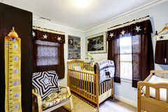 Nursery room interior with crib and rocking chair. And black curtain stock image