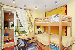 Nursery room interior with two-high wooden bed. Table and window Royalty Free Stock Images