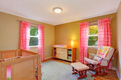Nursery room with pink ruffle curtains. Cozy nursery room with bright pink ruffle curtains. Furnished with dresser, comfortable armchair and crib stock photo
