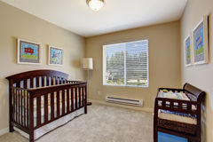 Nursery room in soft beige color with window. Cozy nursery room in soft beige color with crib and changing cabinet stock images