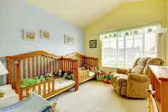 Nursery room with two cribs for twins and lots of toys. Nursery room with two cribs for twins, yellow and blue walls and lots of toys Stock Photo