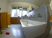 Nursery school bathroom with ceramic sinks. Inside a nursery school bathroom with large ceramic sinks royalty free stock photos