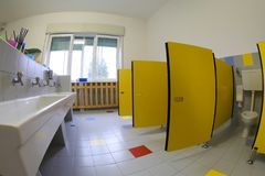 Nursery school bathroom with large ceramic sinks and yellow door. S of caibns stock photo