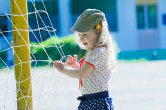 Nursery school girl playing near football goal net with yellow goalposts. Nursery school girl is playing near football goal net with yellow goalposts Royalty Free Stock Photo