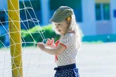 Nursery school girl playing near football goal net with yellow goalposts Royalty Free Stock Photo
