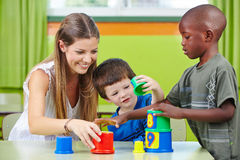 Nursery teacher building tower Royalty Free Stock Images