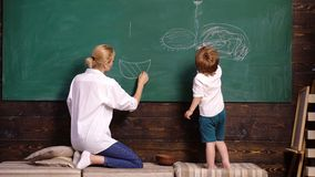 Nursery teacher and child boy painting picture on chalkboard. Woman and boy draw. Mother and son draw with chalk at stock video footage