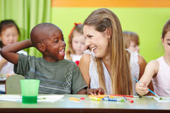 Nursery teacher and children having. Fun together in a kindergarten group Royalty Free Stock Photography