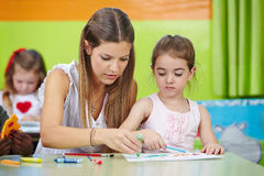 Nursery teacher helping girl Stock Images