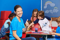Nursery teacher holding thumbs up. With group of children painting in the background Stock Photography