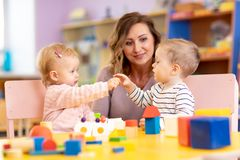 Nursery teacher looking after children in nursery. Little toddlers girl and boy play together with toys. stock images