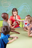 Nursery teacher playing flute Royalty Free Stock Photo