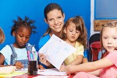Nursery teacher showing drawing in kindergarten Royalty Free Stock Image