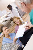 Nurses Being Handed A Clipboard Royalty Free Stock Image