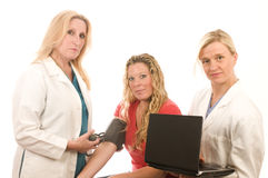 Nurses doctors female with patient. Team of two happy and confident female doctors or nurses medical personnel wearing colorful scrubs clothes and lab coats Royalty Free Stock Image