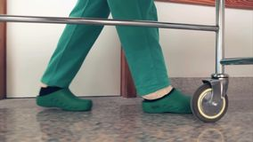 Nurses driving a patient on his bed. In a hallway in a hospital stock video footage