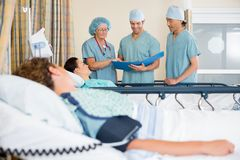 Nurses Examining Patient's Report Stock Photo