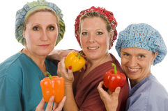 Nurses healthy diet fresh  peppers. Team group of pretty happy and smiling confident nurses promoting healthy diet with fresh colorful bell peppers  while Stock Image