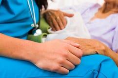 Nurses Helping Elderly. Social care provider holding senior hands in caring attitude - helping elderly people royalty free stock photos
