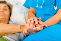 Nurses Helping Elderly. Social care provider holding senior hands in caring attitude - helping elderly people royalty free stock photo