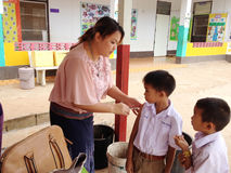 Nurses are injection to protect against measles for children at elementary level at Loei Stock Photo