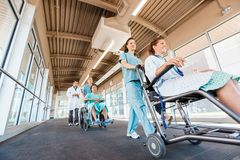 Nurses Pushing Patients On Wheelchairs With Doctor Stock Images